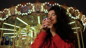 Sip of a hot drink. A young woman with a beautiful smile drinks hot coffee from a paper cup on the background of a carousel. Curly brunette in red take a sip of stock footage