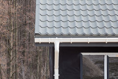SIP panel house construction. New gray metal tile roof with white rain gutter. Stock Photography