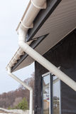 SIP panel house construction. New white rain gutter.  Drainage System with Plastic Siding Soffits and Eaves against blue sky. Stock Photo