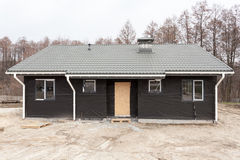 SIP panel house with new gray metal tile roof,white rain gutter and insulation. Stock Photos
