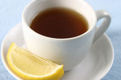 Sip of Tea with Lemon. Hot tea with lemon in a white cup with saucer Royalty Free Stock Photos
