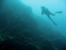 Sipadan wall scuba diver silhouette. Diver scuba diving on steep reef walls of sipadan island marine park in sabah borneo Royalty Free Stock Images