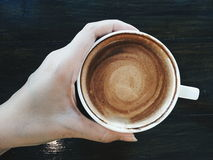 Sipping a good coffee. Hand holding a cup of coffee Stock Photos