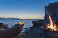 Sipping old fashioned scotch by the sea at the fire pit Stock Images