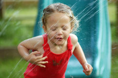 Sipping From A Sprinkler. A young girl attempts to take a sip of water from a lawn sprinkler on a warm, summer evening. After repeated attempts, the girl is Royalty Free Stock Images