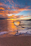 Sipping wine at sunset. Wine glass on the beach in Hawaii at sunset Royalty Free Stock Photography