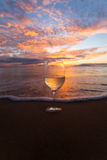 Sipping wine at sunset. Wine glass on the beach in Hawaii at sunset royalty free stock photo