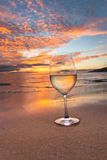 Sipping wine at sunset. Wine glass on the beach in Hawaii at sunset Stock Photo