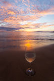 Sipping wine at sunset. Wine glass on the beach in Hawaii at sunset Stock Image