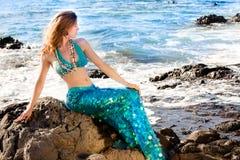 Sirène aux cheveux longs sur des roches de lave à l'océan Photographie stock