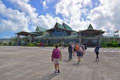 Sir Gaetan Duval lotnisko z przyjeżdżać pasażerów chodzi w dramatycznego niebo z chmurami i budynek Obrazy Stock