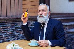 Sir with grey beard drinking coffee while smoking electrocigaret. Mid shot of sir with grey beard drinking coffee while smoking electrocigarette Stock Image