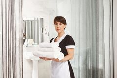 Sir, I will put extra towels in bathroom. Portrait of woman in maid uniform standing with white hotel towels near door. Looking at camera with calm and serious Stock Image