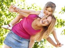 Sira de mãe à doação a sua filha no parque Imagens de Stock