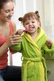 Sira de mãe à escovadela de dentes de ensino da criança da filha no banheiro imagens de stock royalty free