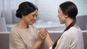 Sira de mãe à fala à filha e a guardar suas mãos, dando o conselho, maternidade vídeos de arquivo