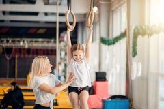 Sira de mãe à filha de ajuda para jogar esportes em anéis ginásticos Fotos de Stock Royalty Free