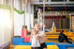 Sira de mãe à filha de ajuda para jogar esportes em anéis ginásticos Imagem de Stock