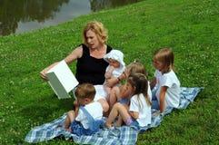 Sira de mãe à leitura às crianças Fotografia de Stock