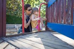 Sira de mãe à menina de ajuda para escalar ao campo de jogos Foto de Stock Royalty Free