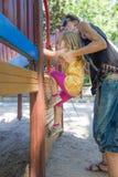 Sira de mãe à menina de ajuda para escalar etapas no campo de jogos Foto de Stock