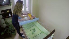 Sira de mãe à obtenção vestido seu bebê com o pano amarelo do corpo 4K video estoque