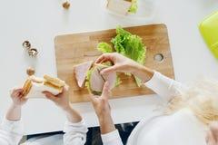 Sira de mãe à opinião superior da cozinha dos sanduíches comer da filha em casa fotos de stock