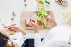Sira de mãe à opinião superior da cozinha dos sanduíches de peru comer da filha em casa Imagem de Stock