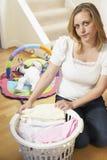 Sira de mãe à roupa de dobramento do bebê em casa Fotografia de Stock Royalty Free