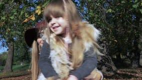 Sira de mãe a abraçar sua filha doce em um parque outonal ensolarado, fora filme