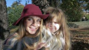 Sira de mãe a abraçar sua filha doce em um parque outonal ensolarado, fora vídeos de arquivo