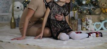 Sira de mãe a abraços e beije a filha no fundo da árvore, dos presentes e dos brinquedos de Natal, sentando-se no assoalho, véspe foto de stock royalty free