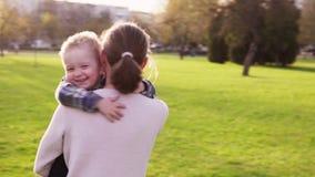 Sira de mãe a abraços e a giros com seu filho pequeno no parque no por do sol video estoque
