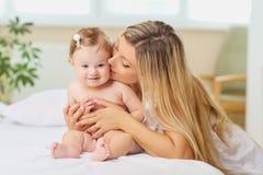 Sira de mãe a abraços uma criança do bebê em uma cama em uma sala dentro Fotografia de Stock