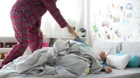 Sira de mãe a acordar seu filho preguiçoso no quarto na manhã filme