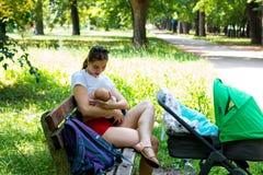 Sira de mãe a amamentar o bebê na natureza que senta-se no banco de parque, ideal bonito do dia de verão para andar com carrinho  fotografia de stock royalty free