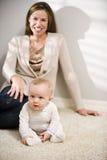 Sira de mãe ao assento no assoalho com o bebê idoso de seis meses Fotografia de Stock