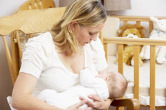 Sira de mãe ao bebê amamentando no berçário Fotografia de Stock Royalty Free