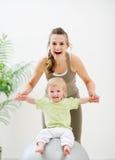 Sira de mãe ao bebê da terra arrendada da matriz que senta-se na esfera da aptidão Foto de Stock Royalty Free