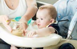 Sira de mãe ao bebê de alimentação com puré do fruto na cozinha Imagens de Stock Royalty Free