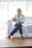Sira de mãe ao bebê de sono da terra arrendada no sofá no quarto ensolarado Imagem de Stock