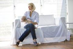 Sira de mãe ao bebê de sono da terra arrendada no sofá no quarto ensolarado Foto de Stock Royalty Free