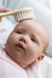 Sira de mãe ao cabelo de arrelia do bebê da mão do ` s com escova de cabelo closeup Materni foto de stock royalty free