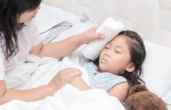 Sira de mãe ao corpo limpado do ` s da filha para reduzir a febre imagens de stock