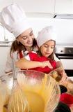 Sira de mãe ao cozimento com a filha pequena no avental e cozinhe queques do molde do enchimento do chapéu com massa do chocolate Foto de Stock