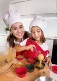 Sira de mãe ao cozimento com a filha pequena no avental e cozinhe queques do molde do enchimento do chapéu com massa do chocolate Fotografia de Stock