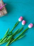 Sira de mãe ao dia do ` s, dia do ` s da mulher tulipas e presentes no fundo de madeira Imagem de Stock