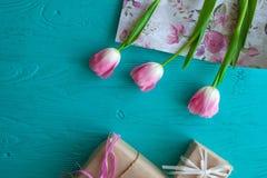 Sira de mãe ao dia do ` s, dia do ` s da mulher tulipas e presentes no fundo de madeira Imagens de Stock