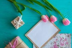 Sira de mãe ao dia do ` s, dia do ` s da mulher tulipas, letra e presentes no fundo de madeira Fotos de Stock