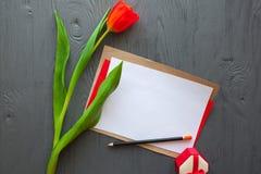 Sira de mãe ao dia do ` s, dia do ` s da mulher tulipas, letra e presentes vermelhos no fundo de madeira Foto de Stock Royalty Free